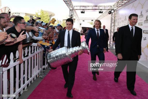 Sidney Crosby of the Pittsburgh Penguins carries the Stanley Cup as he and teammate Carl Hagelin and owner Mario Lemieux of the Penguins arrive at...