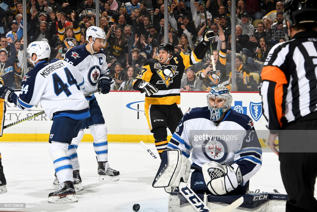 Sidney Crosby #87 of the Pittsburgh Penguins celebrates his 1000th NHL point against Connor Hellebuyck #37 of the Winnipeg Jets at PPG Paints Arena on February 16, 2017 in Pittsburgh, Pennsylvania.