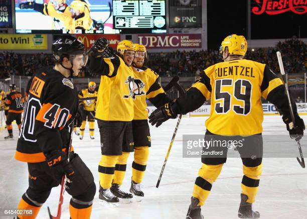 Sidney Crosby of the Pittsburgh Penguins celebrates his first period goal with teammates Scott Wilson and Jake Guentzel as Jordan Weal of the...