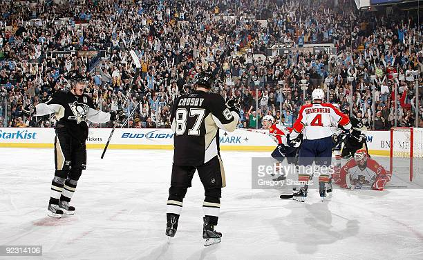 Sidney Crosby of the Pittsburgh Penguins celebrates his goal with Evgeni Malkin in front of Dennis Seidenberg of the Florida Panthers on October 23...
