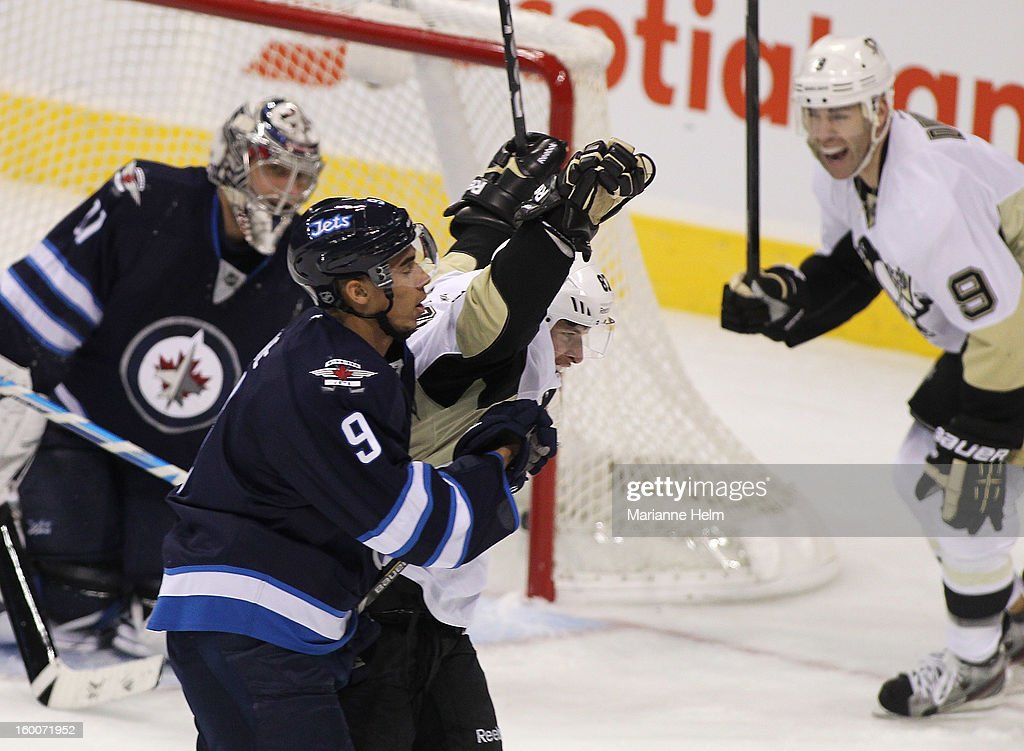 Sidney Crosby #87 of the Pittsburgh Penguins celebrates his second goal of the game while Evander Kane #9 of the Winnipeg Jets reacts during first-period action on January 25, 2013 at the MTS Centre in Winnipeg, Manitoba, Canada.