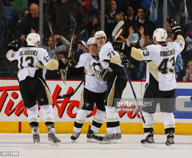 Sidney Crosby of the Pittsburgh Penguins celebrates with Evgeni Malkin after tipping in the winning goal 43 seconds into overtime against the Buffalo...