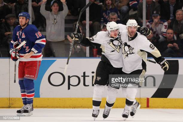 Sidney Crosby of the Pittsburgh Penguins celebrates with Pacal Dupuis after team mate Kris Letang scored a goal against the New York Rangers during...