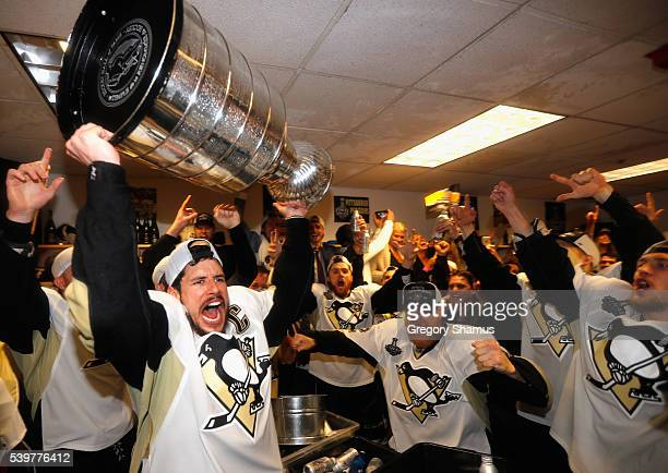 Sidney Crosby of the Pittsburgh Penguins celebrates with the Stanley Cup and teammates in the locker room after winning Game 6 of the 2016 NHL...