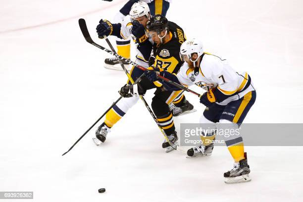 Sidney Crosby of the Pittsburgh Penguins competes for the puck against Matt Irwin and Yannick Weber of the Nashville Predators in Game Five of the...