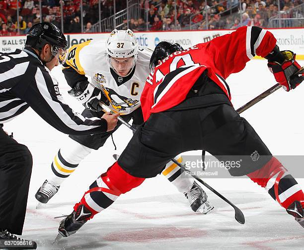 Sidney Crosby of the Pittsburgh Penguins concentrates as he waits for linesman Kory Nagy to drop the puck on a faceoff against Adam Henrique of the...