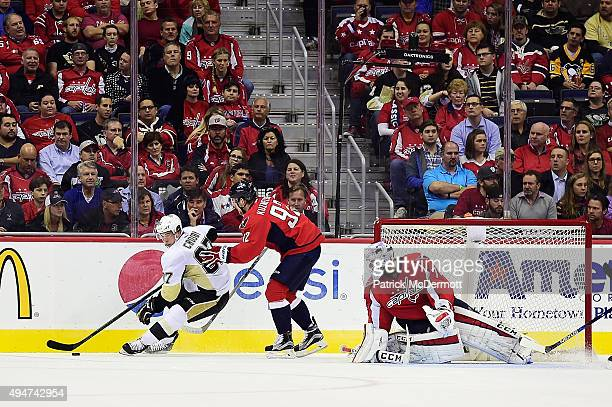 Sidney Crosby of the Pittsburgh Penguins controls the puck against Evgeny Kuznetsov of the Washington Capitals in the first period of an NHL game...