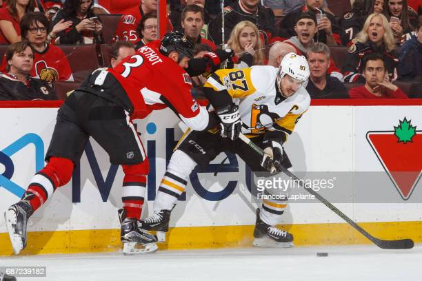 Sidney Crosby of the Pittsburgh Penguins controls the puck against Marc Methot of the Ottawa Senators in Game Four of the Eastern Conference Final...