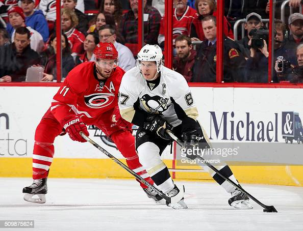 Sidney Crosby of the Pittsburgh Penguins controls the puck away from Jordan Staal of the Carolina Hurricanes during an NHL game at PNC Arena on...