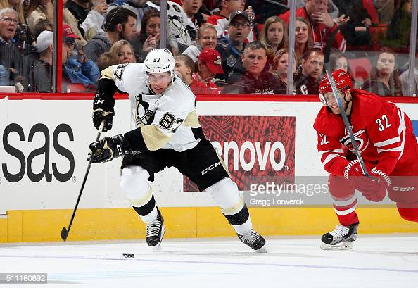 Sidney Crosby of the Pittsburgh Penguins controls the puck away from Kris Versteeg of the Carolina Hurricanes during an NHL game at PNC Arena on...