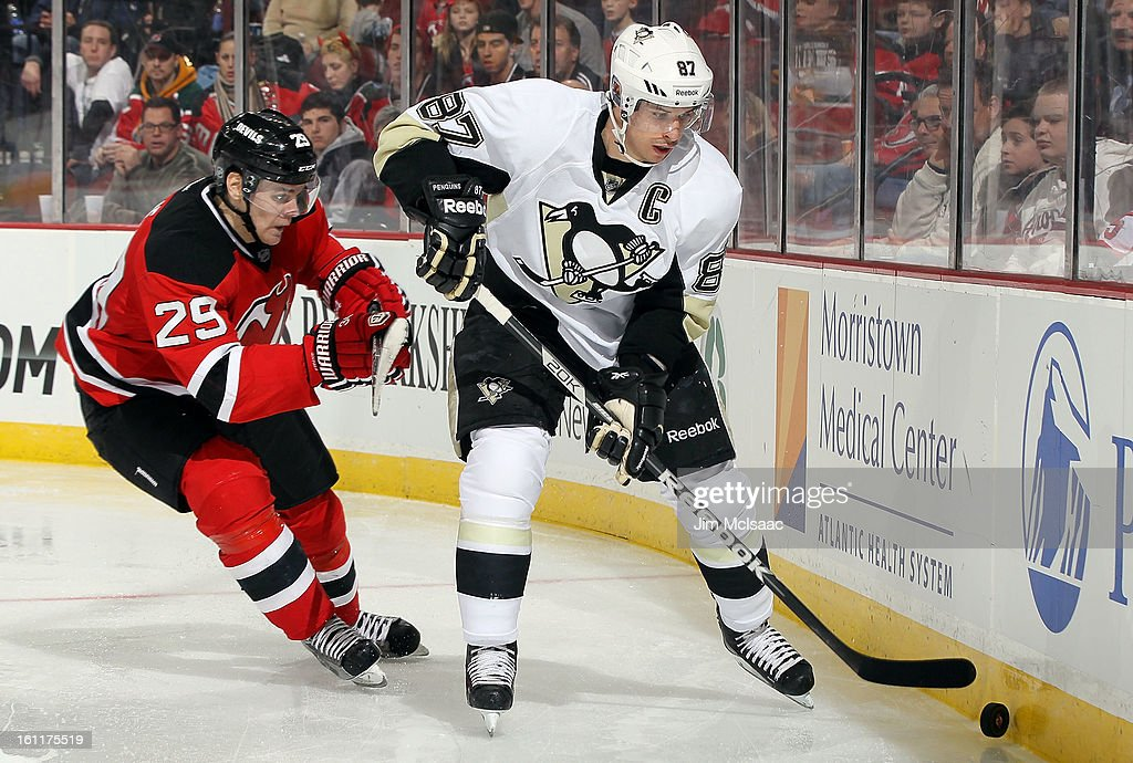 Sidney Crosby #87 of the Pittsburgh Penguins controls the puck behind the net against Mark Fayne #29 of the New Jersey Devils at the Prudential Center on February 9, 2013 in Newark, New Jersey.