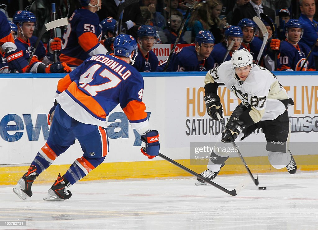 Sidney Crosby #87 of the Pittsburgh Penguins controls the puck in front of Andrew MacDonald #47 of the New York Islanders at Nassau Veterans Memorial Coliseum on Febuary 5, 2013 in Uniondale, New York.