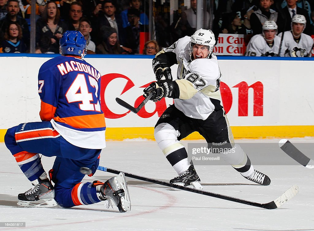 Sidney Crosby #87 of the Pittsburgh Penguins fires the puck past Andrew MacDonald #47 of the New York Islanders in an NHL hockey game at Nassau Veterans Memorial Coliseum on March 22, 2013 in Uniondale, New York. The Penguins defeated the Islanders 4-2.