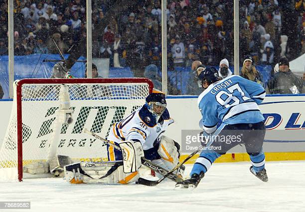Sidney Crosby of the Pittsburgh Penguins gets the puck past goaltender Ryan Miller of the Buffalo Sabres to win the NHL Winter Classic 21 in a shoot...