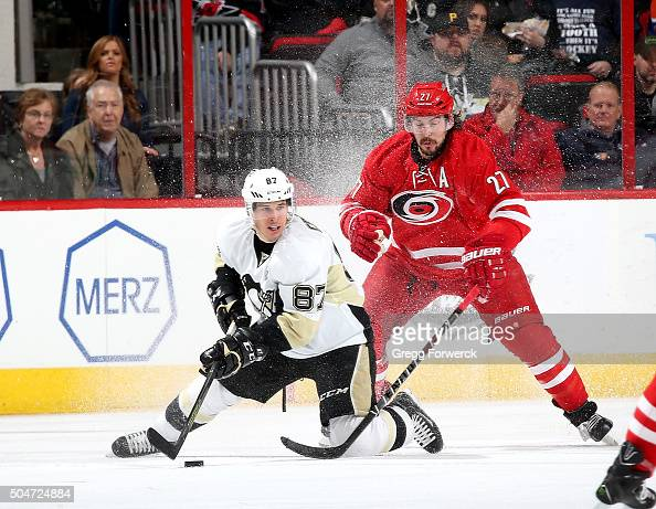 Sidney Crosby of the Pittsburgh Penguins goes down on a knee and maintains control of the puck as Justin Faulk of the Carolina Hurricanes defends...