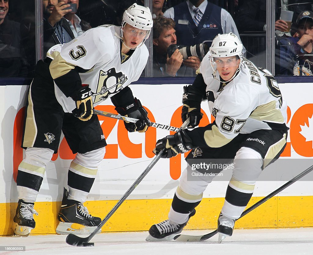 Sidney Crosby #87 of the Pittsburgh Penguins grabs the puck in front of teammate Olli Maatta #3 during an NHL game against the Toronto Maple Leafs at the Air Canada Centre on October 26, 2013 in Toronto, Ontario, Canada. The Leafs defeated the Penguins 4-1.