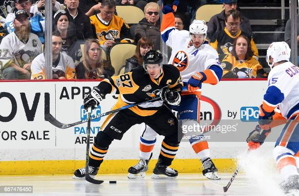 Sidney Crosby of the Pittsburgh Penguins handles the puck against Travis Hamonic of the New York Islanders at PPG Paints Arena on March 24 2017 in...