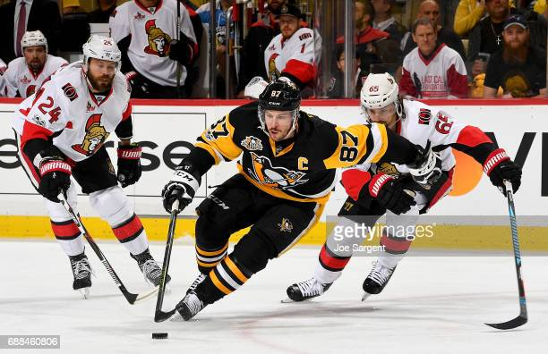 Sidney Crosby of the Pittsburgh Penguins handles the puck between Erik Karlsson and Viktor Stalberg of the Ottawa Senators in Game Seven of the...