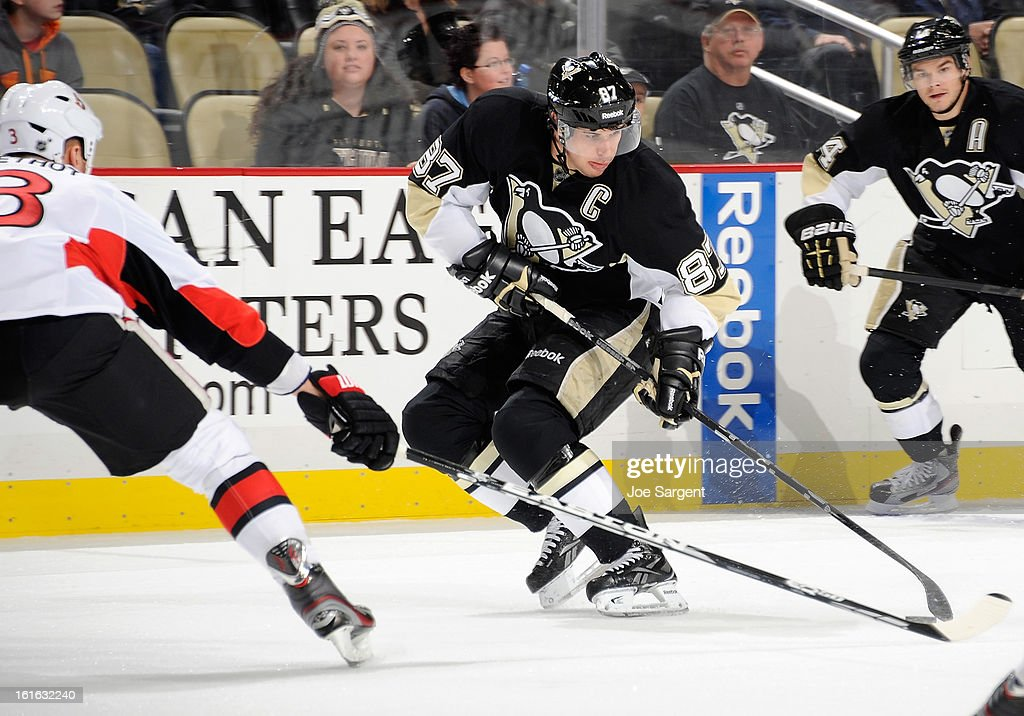 Sidney Crosby #87 of the Pittsburgh Penguins handles the puck in front of the defense of Marc Methot #3 of the Ottawa Senators on February 13, 2013 at Consol Energy Center in Pittsburgh, Pennsylvania.