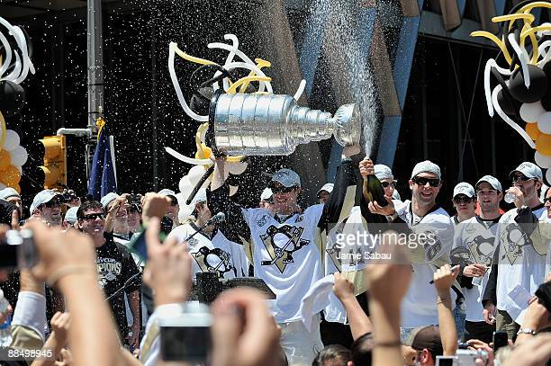 Sidney Crosby of the Pittsburgh Penguins holds the Stanley Cup as Maxime Talbot of the Penguins sprays the crowd during Stanley Cup Champion Victory...