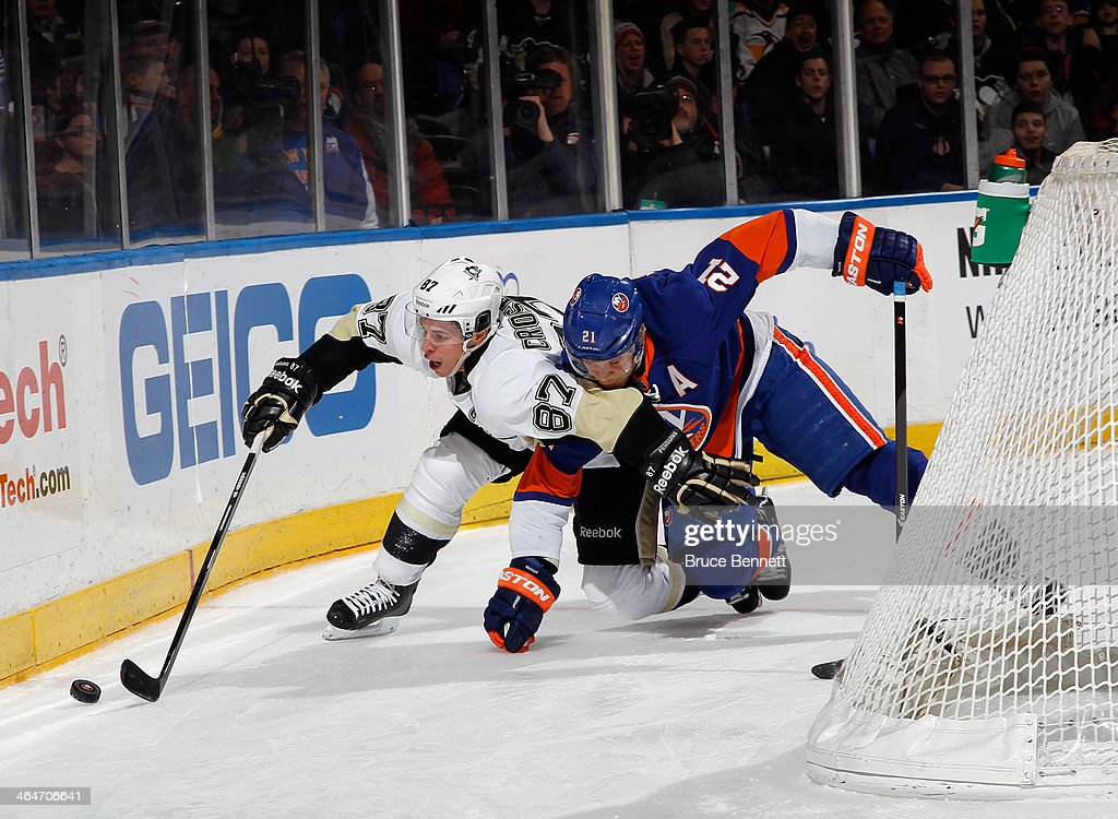 Sidney Crosby of the Pittsburgh Penguins is tied up by Kyle Okposo of the New York Islanders during the third period at Nassau Veterans Memorial...