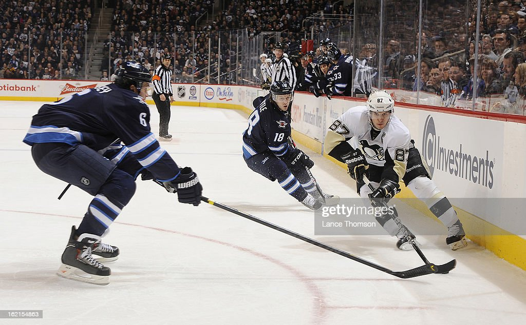 Sidney Crosby #87 of the Pittsburgh Penguins keeps the puck away from Ron Hainsey #6 and Bryan Little #18 of the Winnipeg Jets during third period action at the MTS Centre on February 15, 2013 in Winnipeg, Manitoba, Canada. The Penguins defeated the Jets 3-1.