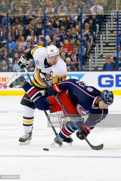 Sidney Crosby of the Pittsburgh Penguins knocks down William Karlsson of the Columbus Blue Jackets while battling for control of the puck during the...