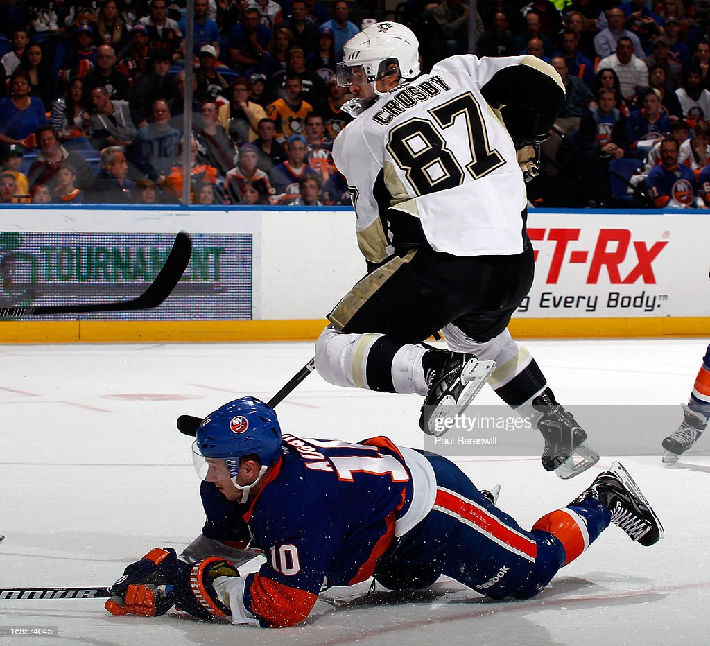 Sidney Crosby #87 of the Pittsburgh Penguins leaps over Keith Aucoin #10 of the New York Islanders as he chases the puck during the third period in Game Six of the Eastern Conference Quarterfinals during the 2013 NHL Stanley Cup Playoffs at Nassau Veterans Memorial Coliseum on May 11, 2013 in Uniondale, New York.