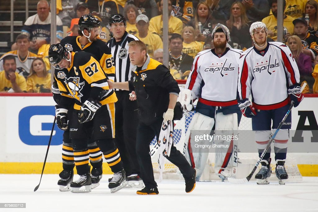 Sidney Crosby #87 of the Pittsburgh Penguins leaves the ice with trainer Chris Stewart after taking a hit in the first period while playing the Washington Capitals in Game Three of the Eastern Conference Second Round during the 2017 NHL Stanley Cup Playoffs at PPG Paints Arena on May 1, 2017 in Pittsburgh, Pennsylvania.