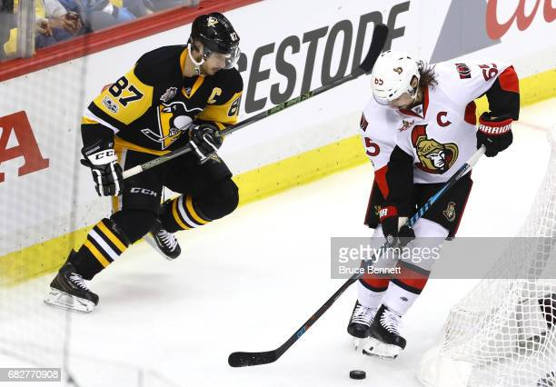 Sidney Crosby of the Pittsburgh Penguins looks for the puck against Erik Karlsson of the Ottawa Senators during the second period in Game One of the...