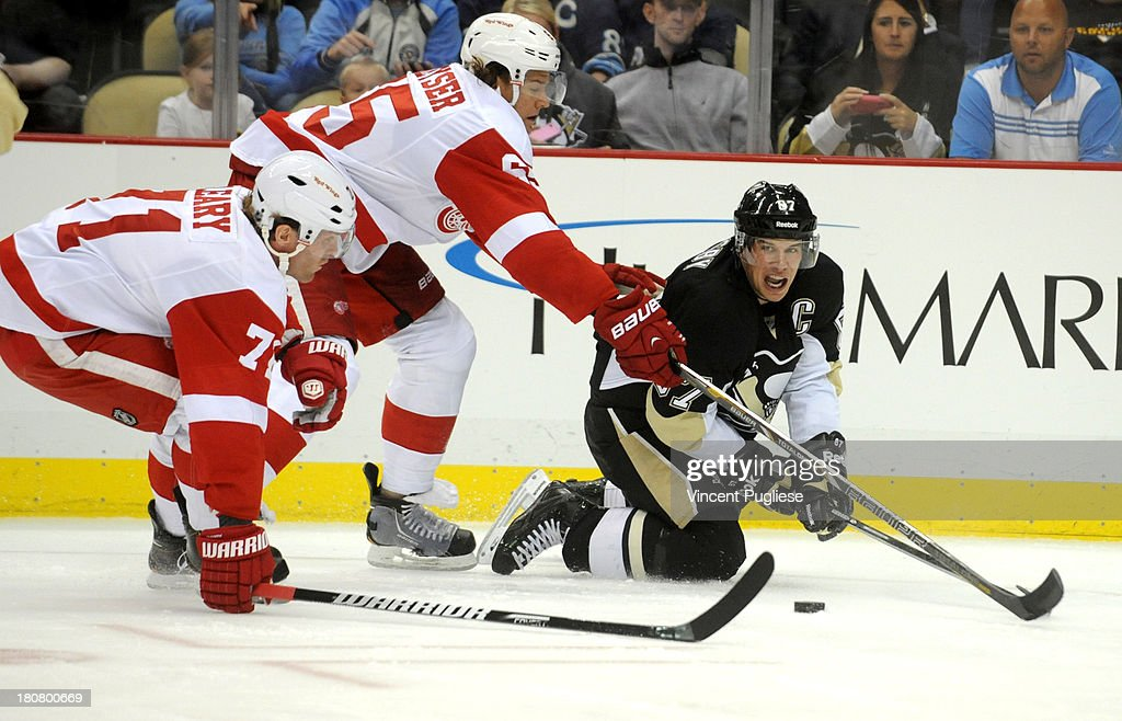 Sidney Crosby #87 of the Pittsburgh Penguins makes a pass past Danny DeKeyser #65 and Daniel Cleary # 71 of the Detroit Red Winds during the first period of a preseason game on September 16, 2013 at the CONSOL Energy Center in Pittsburgh, Pennsylvania.
