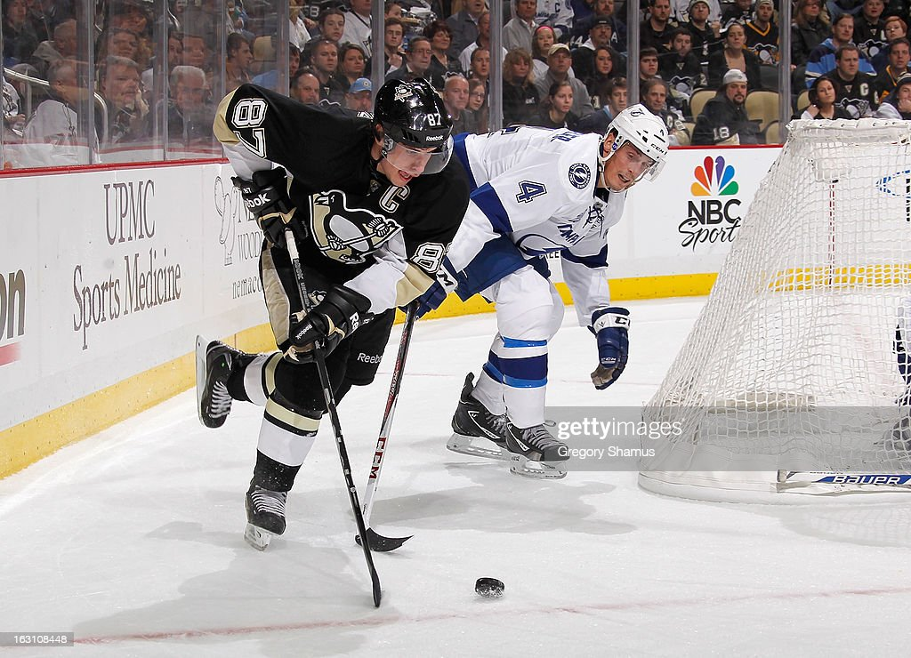 Sidney Crosby #87 of the Pittsburgh Penguins moves the puck in front of the defense of Vincent Lecavalier #4 of the Tampa Bay Lightning on March 4, 2013 at Consol Energy Center in Pittsburgh, Pennsylvania.