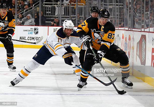 Sidney Crosby of the Pittsburgh Penguins moves the puck in front of David Legwand of the Buffalo Sabres at Consol Energy Center on October 29 2015 in...