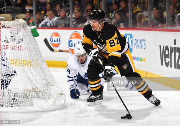 Sidney Crosby of the Pittsburgh Penguins moves the puck in front of Auston Matthews of the Toronto Maple Leafs at PPG Paints Arena on December 9 2017...