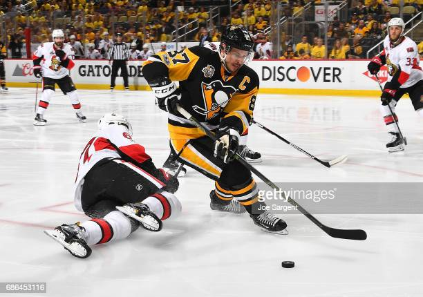 Sidney Crosby of the Pittsburgh Penguins moves the puck past Ben Harpur of the Ottawa Senators in Game Five of the Eastern Conference Final during...