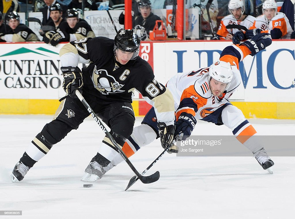 Sidney Crosby of the Pittsburgh Penguins moves the puck past the defense of Mark Streit of the New York Islanders on February 10 2010 at Mellon Arena...
