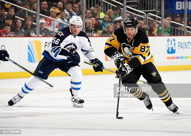 Sidney Crosby of the Pittsburgh Penguins moves the puck up ice in front of Marko Dano of the Winnipeg Jets during the first period at Consol Energy...