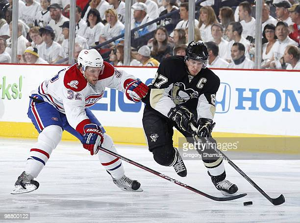 Sidney Crosby of the Pittsburgh Penguins moves the puck up ice in front of Travis Moen of the Montreal Canadiens in Game Two of the Eastern...