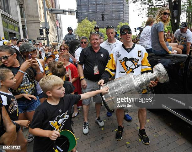 Sidney Crosby of the Pittsburgh Penguins of the Pittsburgh Penguins holds the Stanley Cup for fans to touch during the Victory Parade and Rally on...