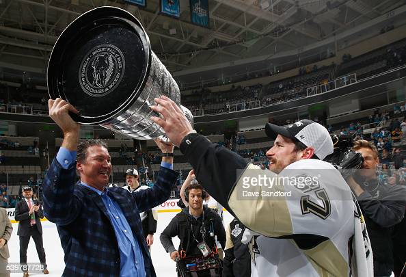 Sidney Crosby of the Pittsburgh Penguins passes the Stanley Cup to coowner and chairman Mario Lemieux after the Penguins won Game 6 of the 2016 NHL...