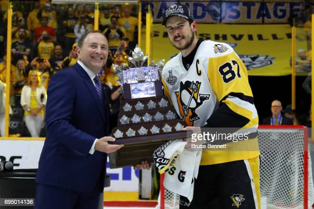 Sidney Crosby of the Pittsburgh Penguins poses for a photo with NHL Commissioner Gary Bettman as he is presented with the Conn Smythe Trophy after...