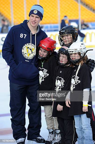 Sidney Crosby of the Pittsburgh Penguins poses for a photo with some kids during a family skate folowing practice for the 2011 NHL Bridgestone Winter...