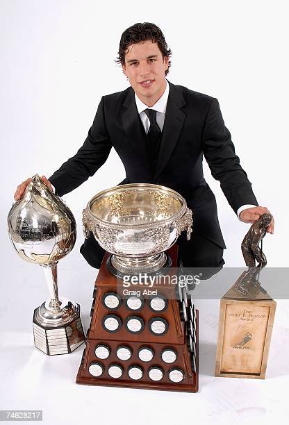 Sidney Crosby of the Pittsburgh Penguins poses for a portrait backstage with the Hart Memorial Trophy the Art Ross Trophy and the Lester B Pearson...