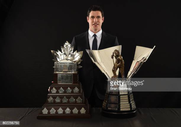 Sidney Crosby of the Pittsburgh Penguins poses for a portrait with the Conn Smythe Trophy and The Maurice 'Rocket' Richard Trophy at the 2017 NHL...