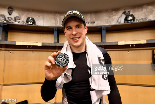 Sidney Crosby of the Pittsburgh Penguins poses with his 1000th point puck after the game against the Winnipeg Jets at PPG Paints Arena on February 16...