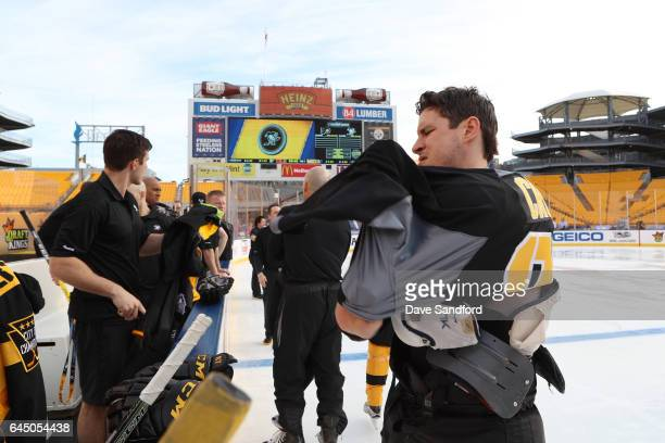 Sidney Crosby of the Pittsburgh Penguins puts on his jersey prior to practice for the 2017 Coors Light NHL Stadium Series game to be played between...