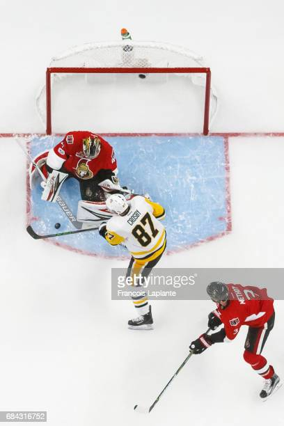 Sidney Crosby of the Pittsburgh Penguins puts the puck in between the pads of Craig Anderson of the Ottawa Senators as Marc Methot defends in Game...