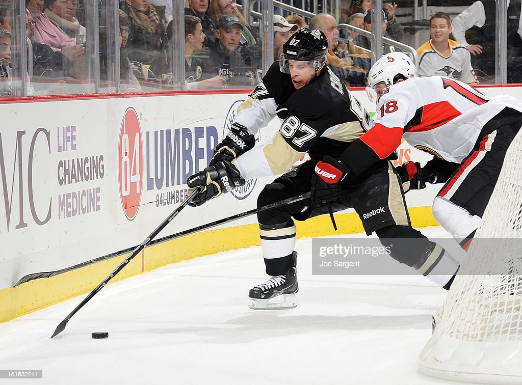 Sidney Crosby #87 of the Pittsburgh Penguins reaches for the loose puck in front of Jim O'Brien #18 of the Ottawa Senators on February 13, 2013 at Consol Energy Center in Pittsburgh, Pennsylvania.