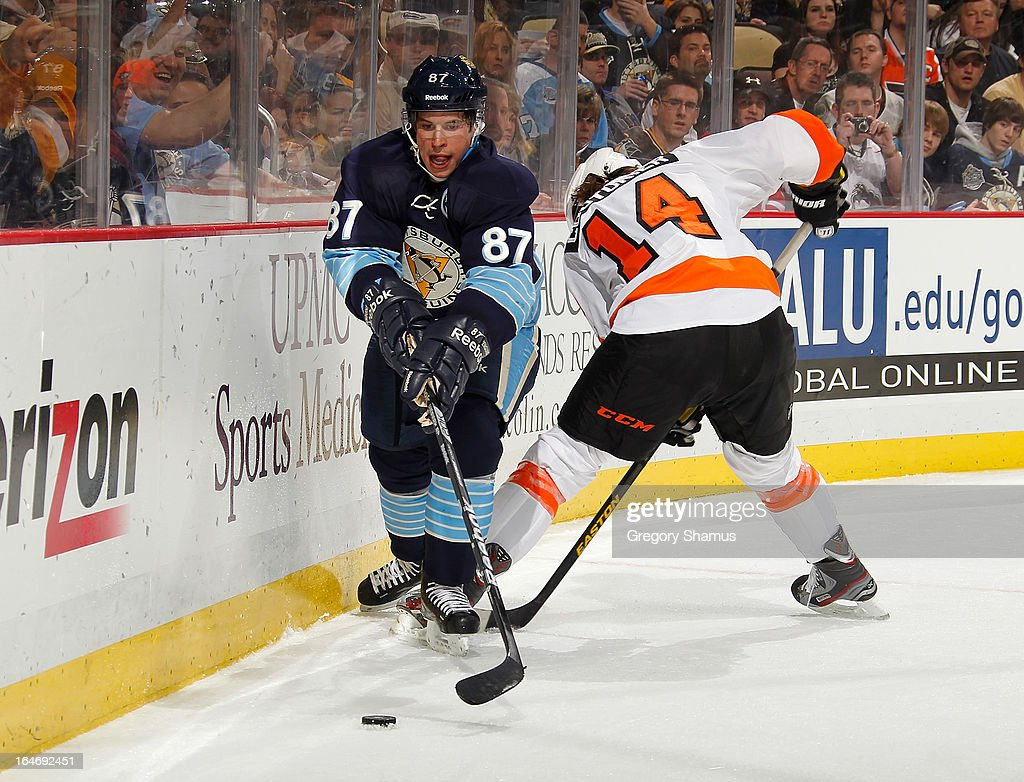 Sidney Crosby #87 of the Pittsburgh Penguins reaches for the loose puck alongside Sean Couturier #14 of the Philadelphia Flyers on March 24, 2013 at Consol Energy Center in Pittsburgh, Pennsylvania.
