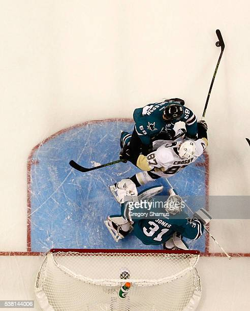 Sidney Crosby of the Pittsburgh Penguins reaches for the puck between the defense of Melker Karlsson and Martin Jones of the San Jose Sharks during...